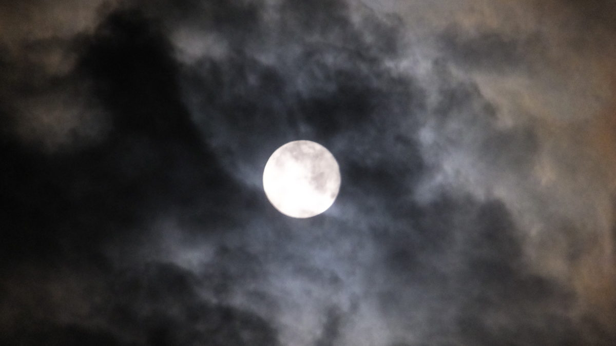 Image of the Moon surrounded by clouds at night